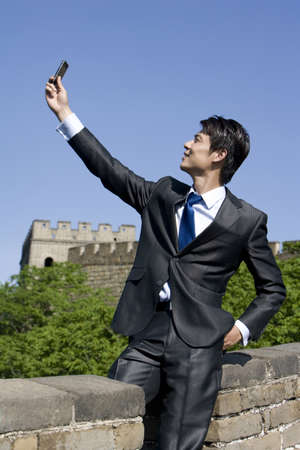 Businessman using a mobile phone on the Great Wall
