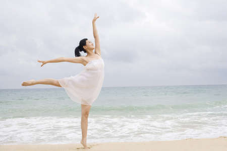 legs apart: A woman dancing at the beach LANG_EVOIMAGES