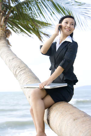context: Businesswoman working on the beach
