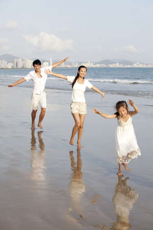 over the edge: Portrait of a family walking on the beach