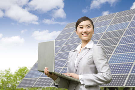 Businesswoman with a laptop in front of solar panels LANG_EVOIMAGES