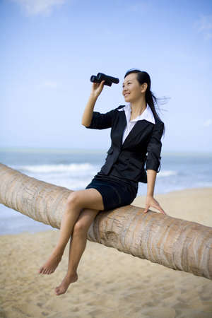 legs crossed at knee: Businesswoman looking through binoculars