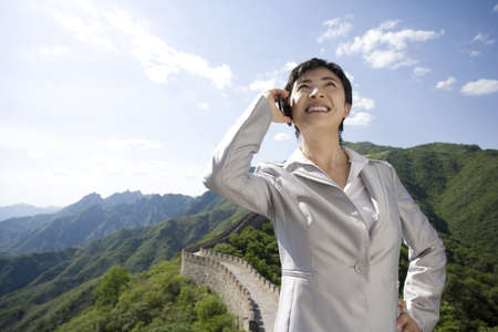 mutianyu: Businesswoman using a mobile phone on the Great Wall