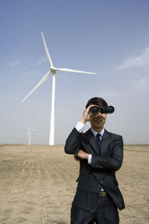 Portrait of a businessman using binoculars in front of wind turbine