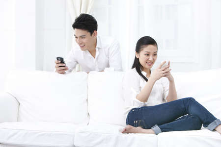 Couple using phones together at home LANG_EVOIMAGES