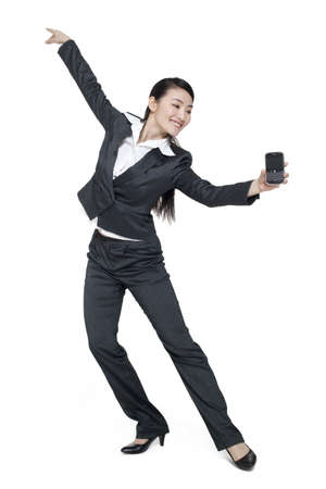 context: A dancing businesswoman holding a mobile phone LANG_EVOIMAGES