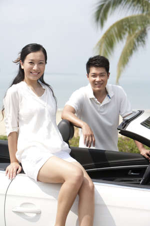 leaning over: Happy Couple Posing In a Convertible