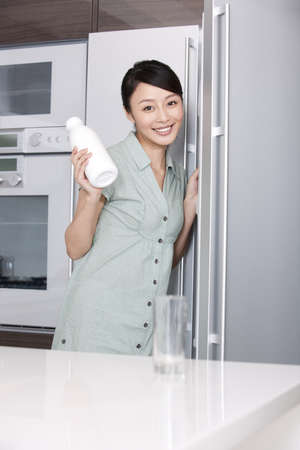 refrigerator: Woman taking milk out of the fridge LANG_EVOIMAGES