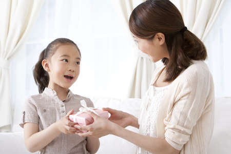Mother and Daughter Exchanging Gifts LANG_EVOIMAGES
