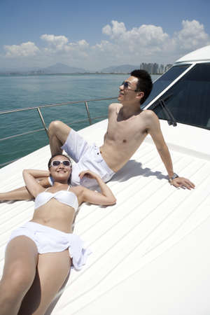 leaning over: Couple Relaxing on a Yacht LANG_EVOIMAGES