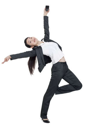 A dancing businesswoman holding a mobile phone LANG_EVOIMAGES