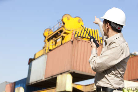 shipping industry worker directing cranes with his walkie-talkie
