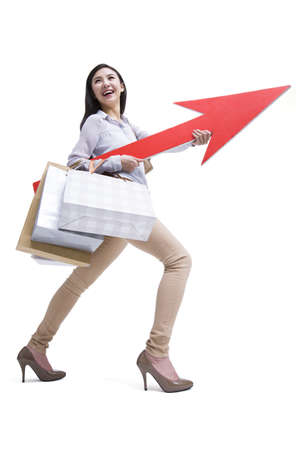 Young woman shopping with red arrow sign in hand LANG_EVOIMAGES