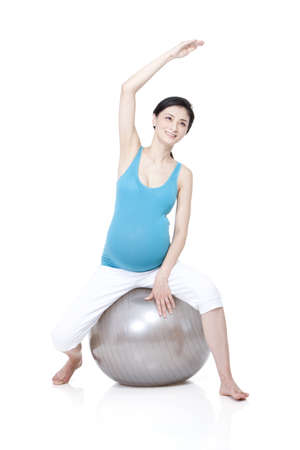Chinese pregnant woman sitting on fitness ball LANG_EVOIMAGES