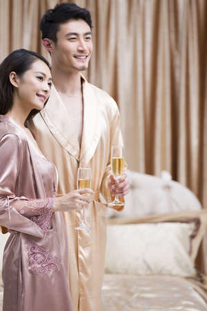 oriental bathrobe: Happy young couple with champagne