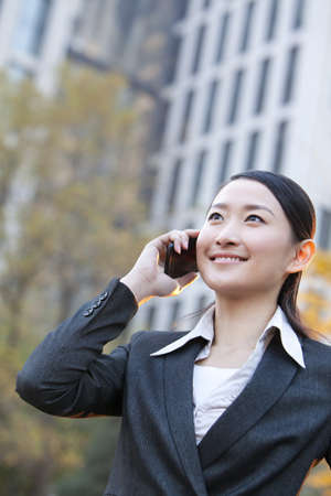 Businesswoman outside office buildings on her mobile phone LANG_EVOIMAGES