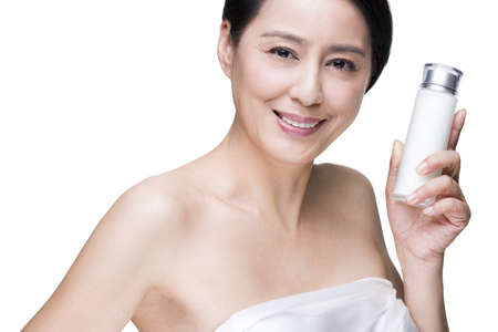 Beautiful mature woman with cosmetic product