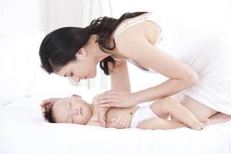 arrodillarse: Madre china tocando el niño durmiendo en casa