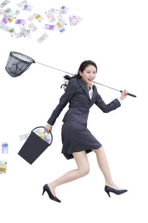 Businesswoman catching money with butterfly net LANG_EVOIMAGES