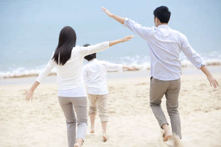 freely: Happy young family pretending to be flying freely on the beach of Repulse Bay,Hong Kong