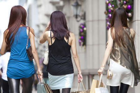 retail scene: Cheerful best female friends go shopping in Hong Kong