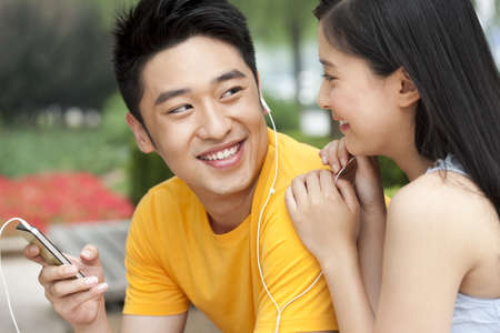 Young couple listening to music on mobile phone outdoors