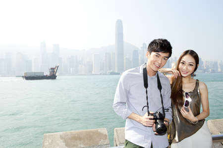 Happy young couple with SLR camera in Victoria Harbor,Hong Kong