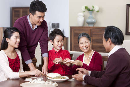 new age: Cheerful family making Chinese dumplings during Chinese New Year LANG_EVOIMAGES