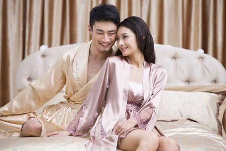 oriental bathrobe: Happy young couple in bedroom