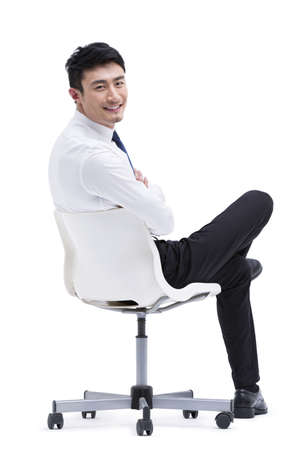 legs crossed at knee: Confident young businessman sitting on chair LANG_EVOIMAGES