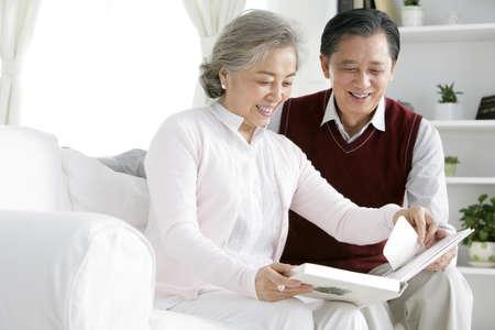 Senior Chinese couple looking at photo album