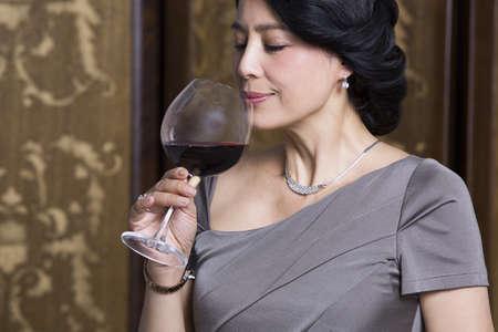 Elegant woman enjoying wine LANG_EVOIMAGES
