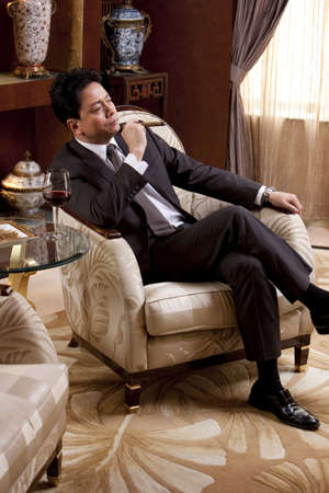 suite: Mature businessman enjoying cigar and wine in a luxurious room LANG_EVOIMAGES