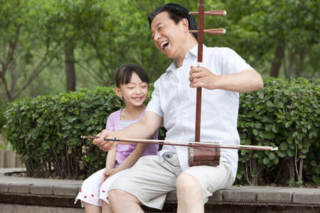 generation gap: Grandfather playing Chinese traditional musical instrument Erhu