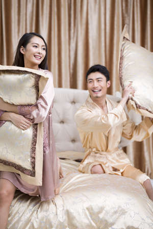 Young couple having pillow fight in bedroom LANG_EVOIMAGES