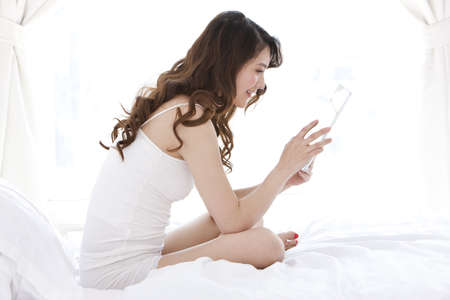 Young woman using digital tablet in bed