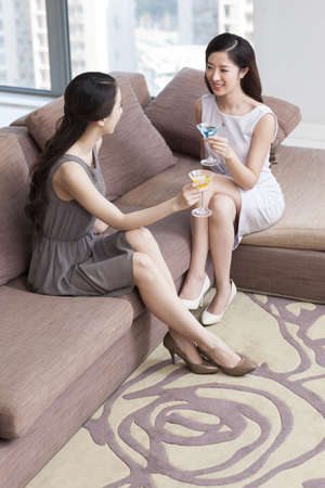 Happy young women drinking cocktail in living room
