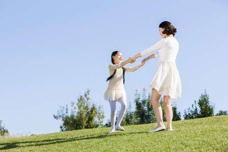 mujer mirando el horizonte: Joven madre e hija jugando en el césped