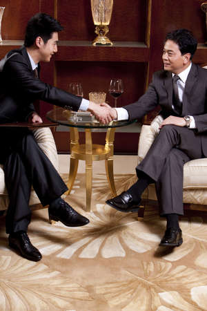 legs crossed at knee: Businessmen shaking hands in a luxurious room LANG_EVOIMAGES