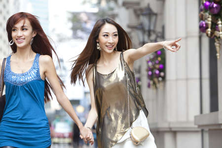 Cheerful best female friends go shopping in Hong Kong