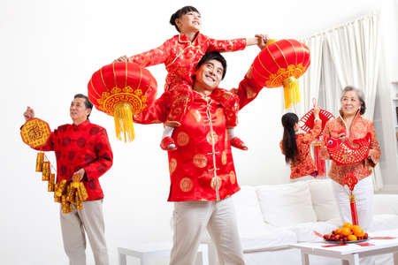 Family putting up Chinese New Year decorations LANG_EVOIMAGES