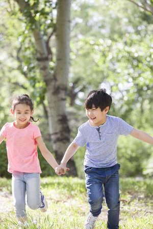 Happy children holding hands running in woods LANG_EVOIMAGES
