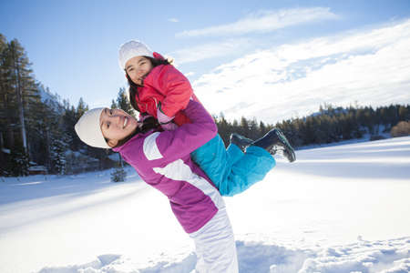 Mother holding daughter aloft on snow ground LANG_EVOIMAGES