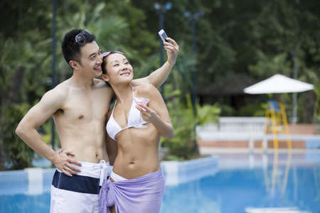 Young couple taking a picture at the poolside