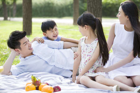 girl in full growth: Happy young family having picnic on grass