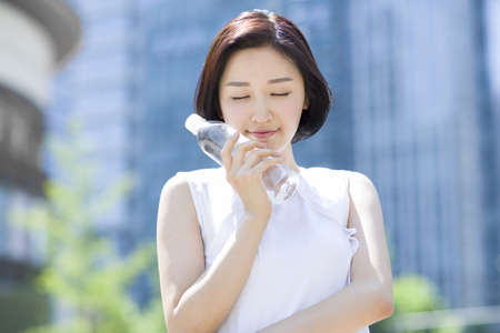 Happy young woman holding bottled water LANG_EVOIMAGES