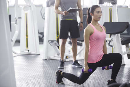 low section: Young woman working with trainer at gym