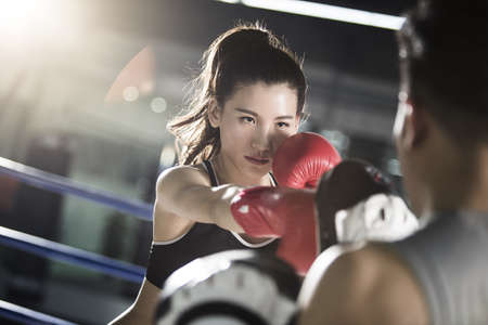 Female boxer training with coach LANG_EVOIMAGES
