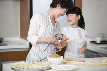 pin board: Happy grandmother and granddaughter making dumplings LANG_EVOIMAGES