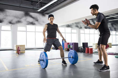 legs apart: Young man working with trainer at gym